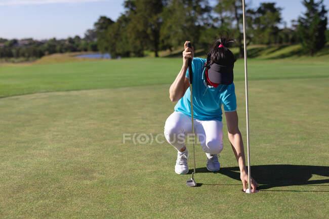 Белая женщина в маске забирает мяч из лунки на поле для гольфа. спорт досуг хобби гольф здоровый открытый образ жизни гигиена во время коронавируса ковид 19 пандемии. — стоковое фото