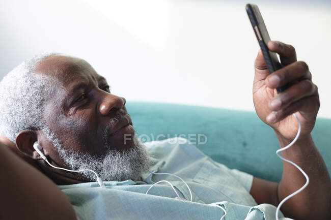 Senior african american man lying on couch using smartphone listening to music on earphones. staying at home in self isolation during quarantine lockdown. — Stock Photo