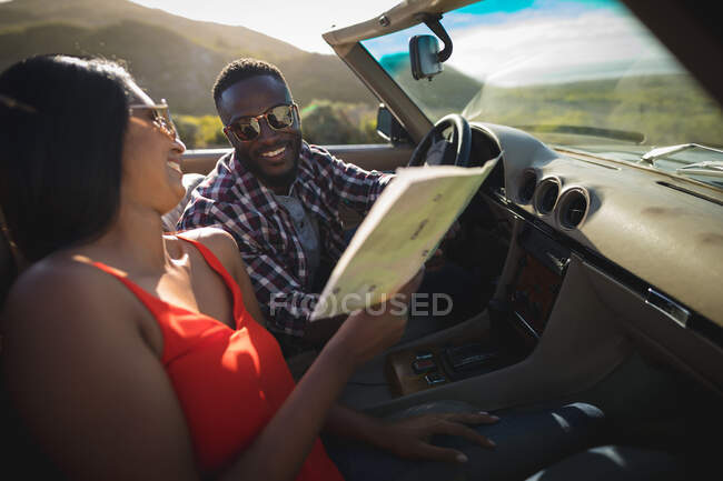 Diverse couple on sunny day sitting in convertible car looking at a map. Summer road trip on a country highway by the coast. — Stock Photo