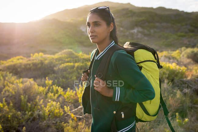 Donna razza mista indossa uno zaino ed escursioni in montagna lungo la costa. L'estate viaggia su un'autostrada di paese dalla costa. — Foto stock