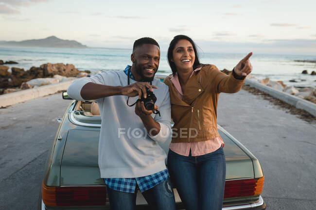 Разнообразная пара, стоящая у кабриолета и фотографирующая с камерой. Летняя поездка по загородному шоссе у побережья. — стоковое фото