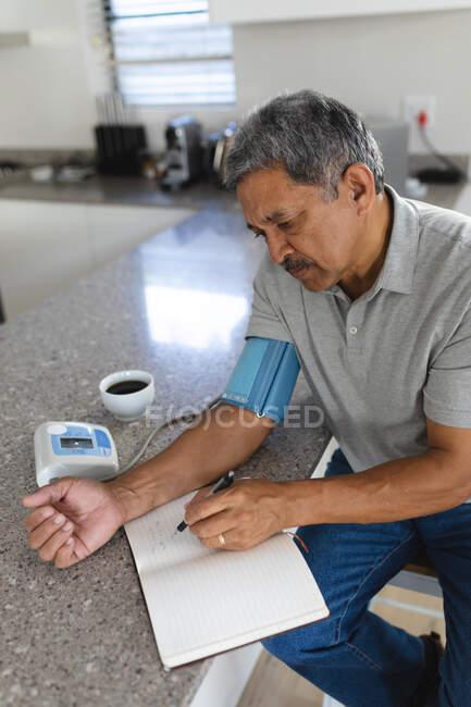 Старший расист дома измеряет давление и записывает его. медицинское обслуживание на дому во время карантинной изоляции. — стоковое фото