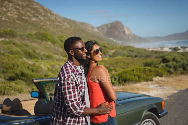 Різноманітна пара в сонячний день стоїть, тримаючи кабріолет в обіймах і посміхаючись. Літня подорож по сільській автостраді біля узбережжя.. — стокове фото