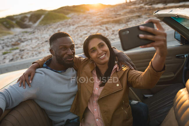 Diverse Paare sitzen in einem Cabrio und machen ein Selfie. Sommer-Roadtrip auf der Landstraße an der Küste. — Stockfoto