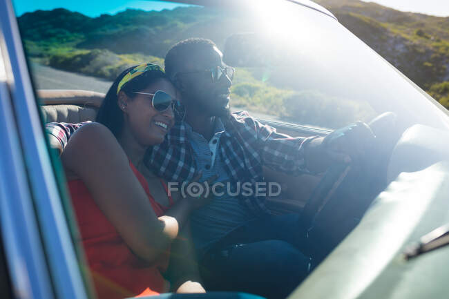 Diverse couple driving on sunny day in convertible car embracing and smiling. summer road trip on a country highway by the coast. — Stock Photo
