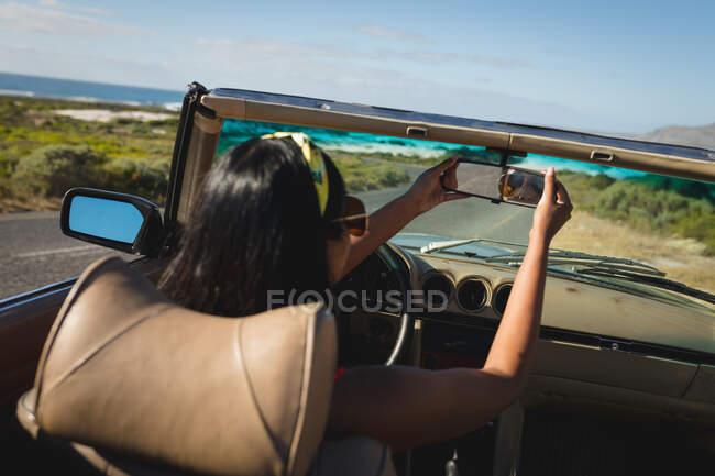 Смешанная расовая женщина за рулем в солнечный день в кабриолете делает селфи. Летняя поездка по загородному шоссе у побережья. — стоковое фото