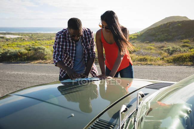 Разнообразная пара в солнечный день стоит у конвертируемой машины, глядя на карту. летняя поездка по сельской дороге на побережье. — стоковое фото