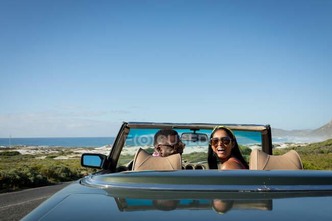 Разнообразная пара в солнечный день едет в перевернутой машине, смотрит на камеру и улыбается. Летняя поездка по загородному шоссе у побережья. — стоковое фото