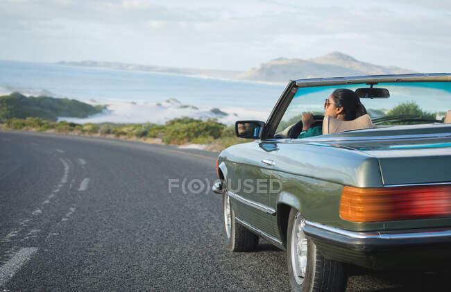 Змішана гоночна жінка їде в сонячний день в кабріолеті, тримаючи кермо. Літня подорож по сільській автостраді біля узбережжя.. — стокове фото