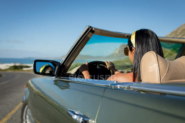 Mixed race woman driving on sunny day in convertible car holding driving wheel. summer road trip on a country highway by the coast. — Stock Photo