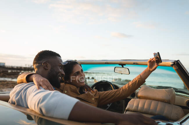 Різноманітна пара сидить у кабріолеті і бере селфі. Літня подорож по сільській автостраді біля узбережжя.. — стокове фото