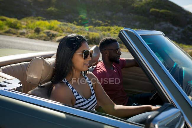 Diversa pareja conduciendo en día soleado en coche convertible hablando y sonriendo. Viaje de verano por carretera en una carretera rural junto a la costa. - foto de stock