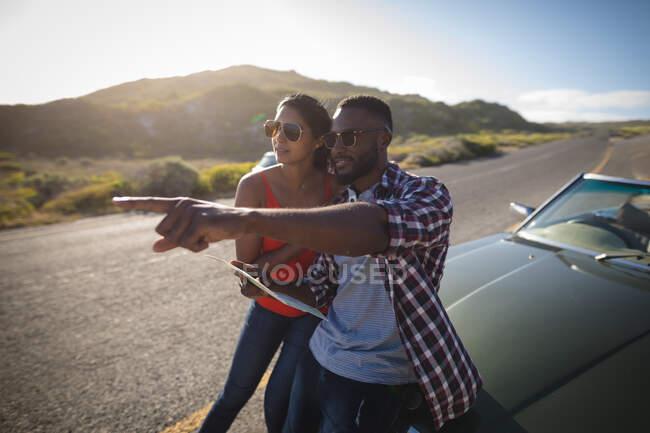 Різноманітна пара в сонячний день стоїть біля кабріолетної машини, дивлячись на мапу. Літня подорож по сільській автостраді біля узбережжя.. — стокове фото