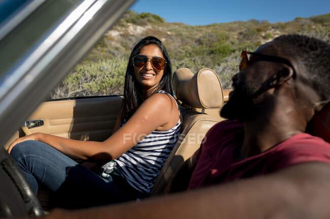 Різні подружжя їдуть у сонячний день у конвертованій машині, дивлячись один на одного і посміхаючись. Літня подорож по сільській автостраді біля узбережжя.. — стокове фото
