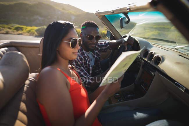 Разнообразная пара в солнечный день сидит в конвертируемой машине, глядя на карту. летняя поездка по сельской дороге на побережье. — стоковое фото