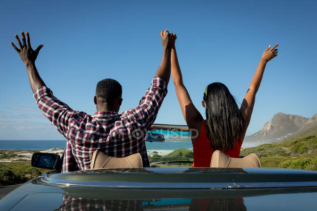 Diverse couple driving on sunny day in convertible car holding their hands up. summer road trip on a country highway by the coast. — Stock Photo