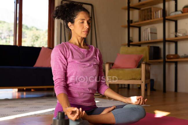 Белая женщина с закрытыми глазами медитирует, практикует йогу дома. Оставаться дома в изоляции во время карантинной изоляции. — стоковое фото