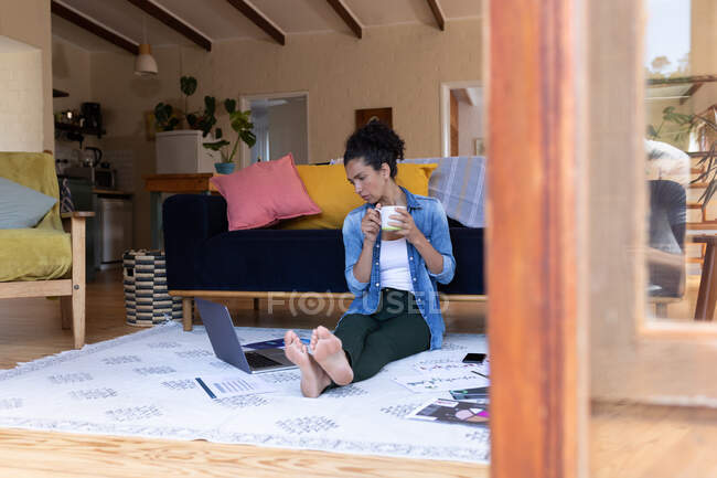 Белая женщина, сидящая на полу, держа чашку кофе, работает из дома. Оставаться дома в изоляции во время карантинной изоляции. — стоковое фото
