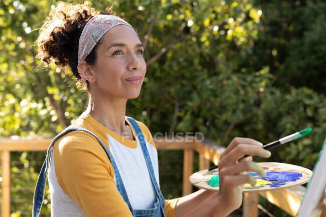 Kaukasische Frau beim Malen im Freien an einem sonnigen Tag. Zu Hause bleiben in Selbstisolierung während Quarantäne Lockdown. — Stockfoto