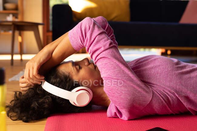 Кавказька жінка лежала на підлозі з навушниками, розслабляючись удома. Перебуваючи вдома в ізоляції під час карантину.. — стокове фото