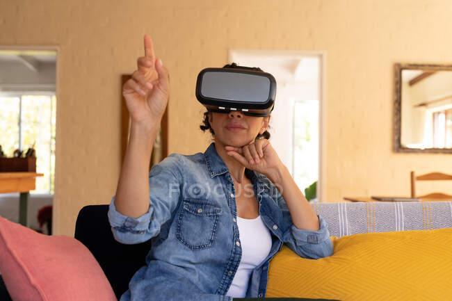 Mulher caucasiana vestindo vr fone de ouvido sentado no sofá em casa. Ficar em casa em auto-isolamento durante o bloqueio de quarentena. — Fotografia de Stock
