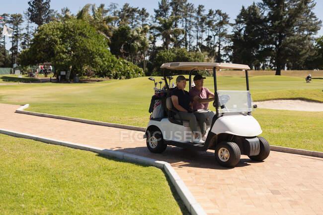 Kaukasische Seniorinnen und Senioren, die Golf-Buggy auf dem Golfplatz fahren, reden und lächeln. Golf-Sport-Hobby, gesunder Lebensstil im Ruhestand. — Stockfoto