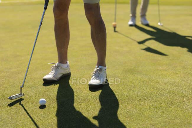 Старший человек смотрит, как другие готовятся стрелять в зеленый. Хобі для гольфу, здоровий спосіб життя на пенсії. — стокове фото