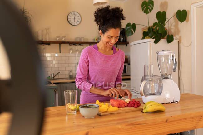 Mulher caucasiana feliz vlogging, corte de frutas na cozinha em casa. Ficar em casa em auto-isolamento durante o bloqueio de quarentena. — Fotografia de Stock