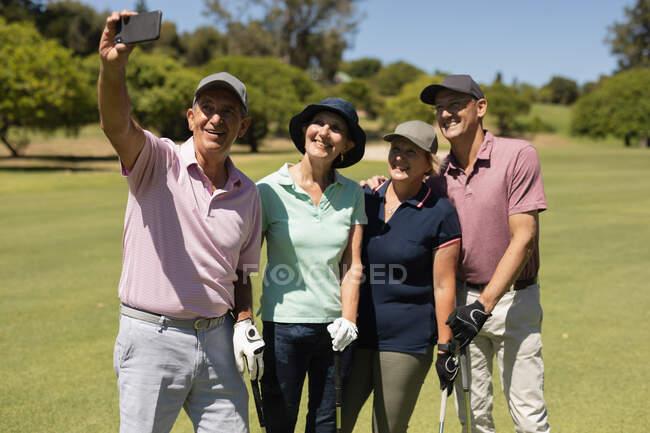 Четыре белых старших мужчины и женщины держат клюшки для гольфа и делают селфи. Спортивное увлечение гольфом, здоровый пенсионный образ жизни — стоковое фото