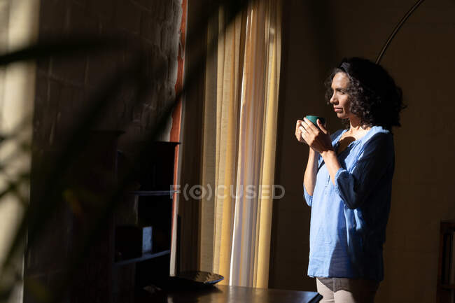 Задумчивая белая женщина с зеленой кружкой, смотрящая в окно дома. Оставаться дома в изоляции во время карантинной изоляции. — стоковое фото