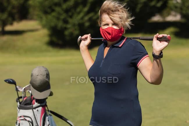 Kaukasische Seniorin mit Gesichtsmaske hält Golfschläger in die Kamera. Golf Sport Hobby, gesunder Lebensstil im Ruhestand während Coronavirus covid 19 Pandemie. — Stockfoto