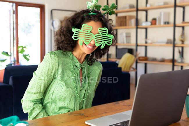 Femme caucasienne vêtue de vert avec des lunettes de trèfle faisant appel à la vidéo du jour de st Patrick. rester à la maison en isolement personnel pendant le confinement en quarantaine. — Photo de stock