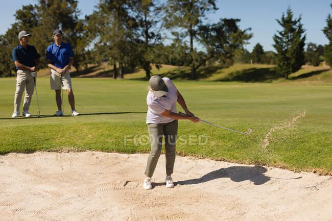 Двоє старшокласників спостерігали за жінкою, яка тримала гольф-клуб, готуючись стріляти в бункер. Гольф спорт хобі, здоровий спосіб життя на пенсії. — стокове фото