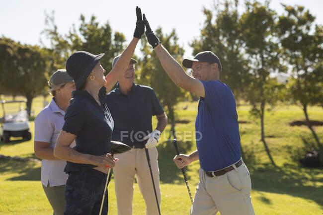 Чотири старші кавказькі чоловіки і жінки високого рівня фінішера тримають ключки для гольфу. Гольф спорт хобі, здоровий спосіб життя на пенсії — стокове фото