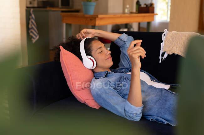 Кавказька жінка лежала на дивані з навушниками, розслабляючись удома. Перебуваючи вдома в ізоляції під час карантину.. — стокове фото