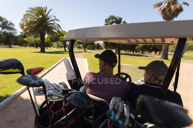 Белый мужчина и женщина за рулем гольф-багги на поле для гольфа разговаривают и улыбаются. Спортивное увлечение гольфом, здоровый пенсионный образ жизни. — стоковое фото