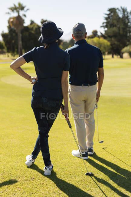 Старший кавказский мужчина и женщина готовятся к выстрелу на зеленой. гольф-спортивное хобби, здоровый пенсионный образ жизни — стоковое фото