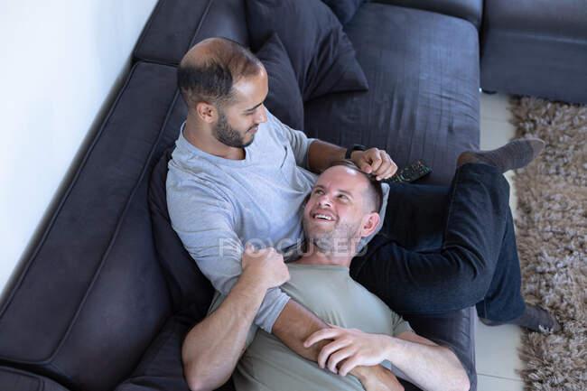 Multi-ethnische schwule männliche Paare sitzen auf der Couch und umarmen sich zu Hause. Genießen Sie die Zeit zu Hause in Selbstisolierung während der Quarantäne Lockdown. — Stockfoto
