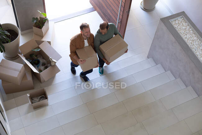 Multi ethnic gay male couple holding boxes walking up the stairs at home. Enjoying time staying at home in self isolation during quarantine lockdown. — Stock Photo