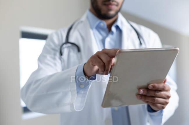 Misto razza maschile medico utilizzando tablet digitale. Protezione igienica durante la pandemia di coronavirus covid 19. — Foto stock