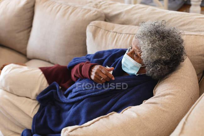 Mujer anciana afroamericana enferma con máscara facial acostada en el sofá. permanecer en casa en aislamiento durante la pandemia de covid-19 - foto de stock