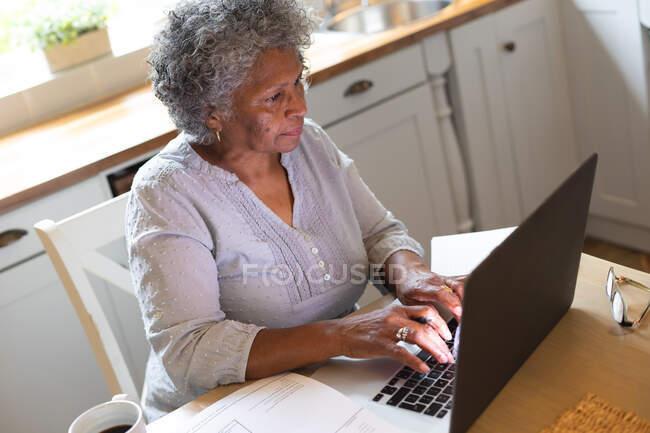 Задумчивая африканская старшая женщина использует ноутбук дома. оставаться дома в изоляции в карантинной изоляции — стоковое фото
