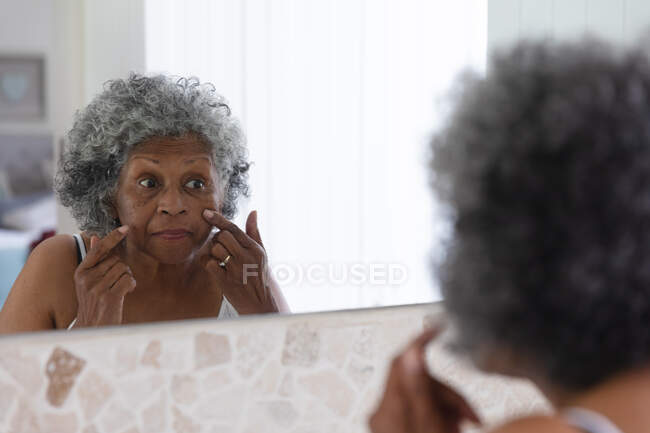 African american senior woman touching her face while looking in the mirror at home. staying at home in self isolation in quarantine lockdown — Stock Photo