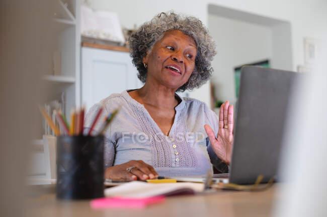 Mulher idosa afro-americana a fazer uma videochamada no portátil em casa. ficar em casa em auto-isolamento em quarentena — Fotografia de Stock
