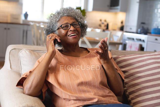 Африканская старшая женщина улыбается, разговаривая по смартфону дома. оставаться дома в изоляции в карантинной изоляции — стоковое фото