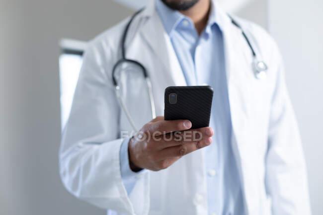 Médico masculino de raza mixta que usa mascarilla facial usando smartphone. higiene protección sanitaria durante la pandemia del coronavirus covid 19. - foto de stock