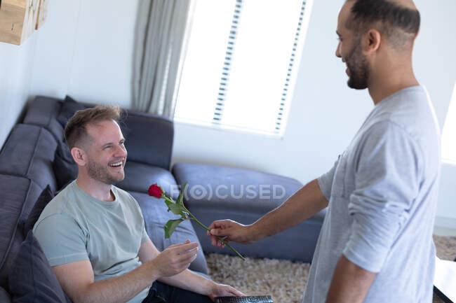 Ein multiethnisches schwules Paar schenkt dem anderen zu Hause eine Rose. Zeit zu Hause in Selbstisolierung während der Quarantäne genießen. — Stockfoto