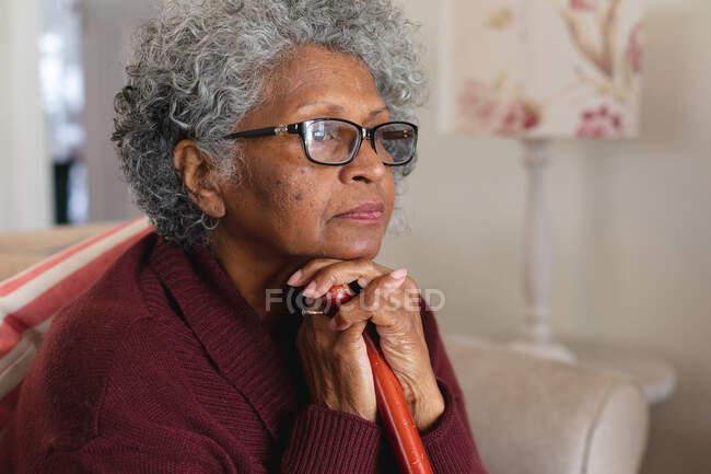 Крупным планом вдумчивой афро-американской пожилой женщины, держащей трость дома. оставаться дома в изоляции в карантинной изоляции — стоковое фото
