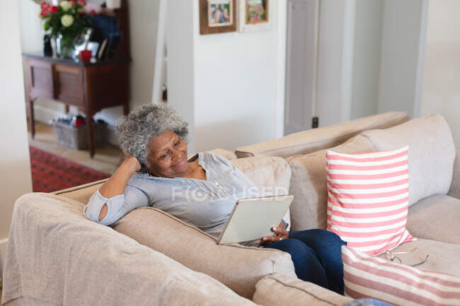 African american senior woman smiling while having a video call on digital tablet at home. staying at home in self isolation in quarantine lockdown — Stock Photo