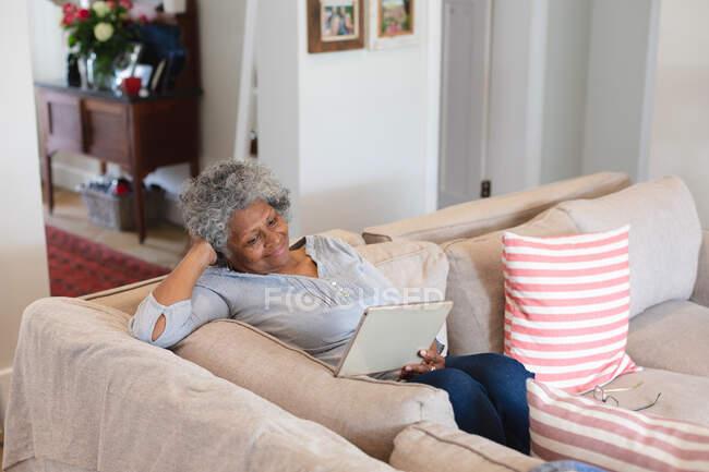 Eine afroamerikanische Seniorin lächelt, während sie zu Hause ein Videotelefon auf einem digitalen Tablet führt. Zu Hause bleiben in Selbstisolierung in Quarantäne — Stockfoto